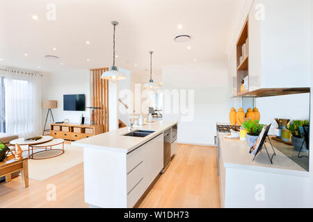 A combined view of a living area with a wall mounted tv and a lamp beside it and a modular kitchen featuring a stylish kitchen island. - Stock Photo
