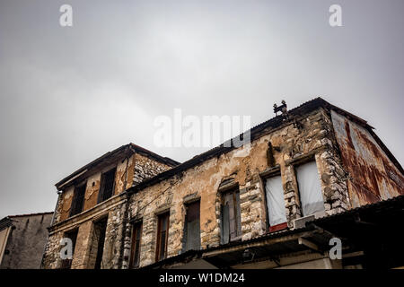 Old Greek industrial building under construction with bricks visible, Ioannina downtown, Greece. Moody foggy spring morning, no people - Stock Photo