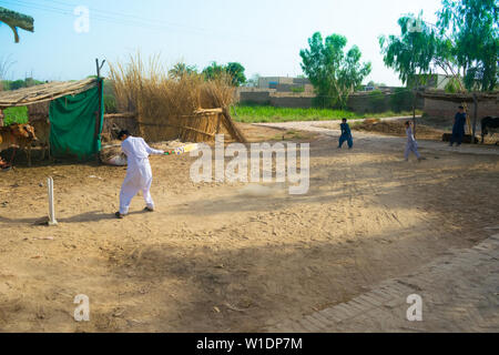 rahimyar khan,punjab,pakistan-july 1,2019:some local boys playing cricket in a village,batsman is bowlled. - Stock Photo