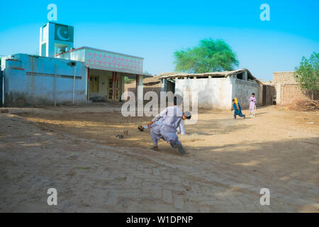 rahimyar khan,punjab,pakistan-july 1,2019:some local boys playing cricket in a village,fielder is trying to catch the ball. - Stock Photo