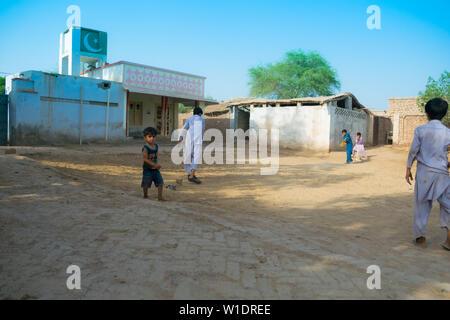 rahimyar khan,punjab,pakistan-july 1,2019:some local boys playing cricket in a village,batsman playing a shot. - Stock Photo