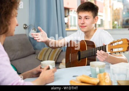 Cheerful teenage boy with guitar friendly talking to his mother at home table - Stock Photo