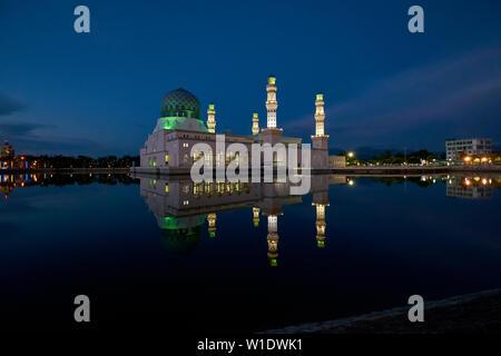 The Moorish style main city Mosque, Masjid Bandaraya, reflected at dusk in Kota Kinabalu, Borneo, Malaysia. - Stock Photo