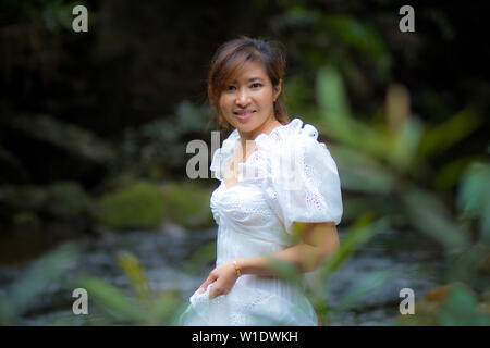beautiful asian younger woman wearing white dress standing in green natural background - Stock Photo