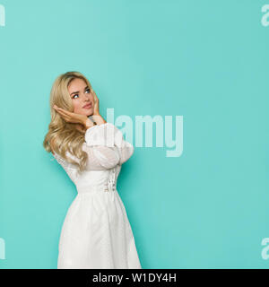 Pensive beautiful blond woman in white lace dress is holding head in hands and looking up. Three quarter length studio shot on turquoise background. - Stock Photo