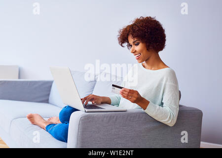 Happy young african woman doing online payments with her credit card and laptop - Stock Photo