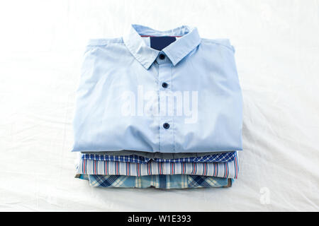 close up of ironed and folded shirts on table at home - Stock Photo