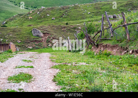 Weathered narrow road, building and fence in summer mountains - Stock Photo