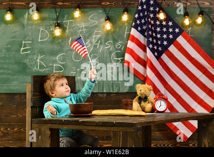 kid in elementary school on the USA national flag background. Pupil with flag of the USA. - Stock Photo