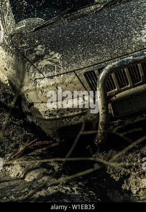 Fragment of car stuck in dirt on sunny autumn day, close up. Wheel in deep rut goes through puddle of mud. Extreme entertainment and driving concept. - Stock Photo