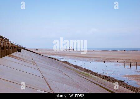 Heavy machinery on the beach by the new flood defences and sloping concrete revetment on the Lancashire Fylde coast at Cleveleys - Stock Photo