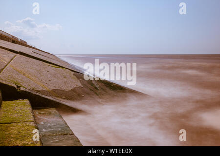 A long exposure of the sea water and waves hitting a sloping concrete revetment or seawall as part of the coastal flood defences - Stock Photo