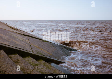 Sea water and waves hitting a sloping concrete revetment or seawall as part of the coastal flood defences - Stock Photo