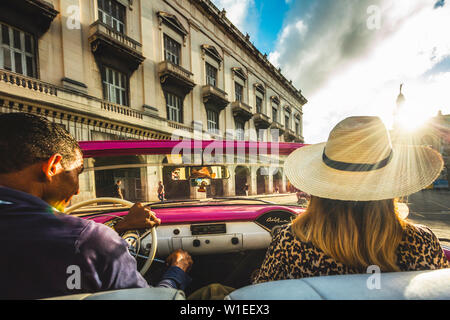 Tourist enjoying classic car ride at sunset in La Habana (Havana), Cuba, West Indies, Caribbean, Central America - Stock Photo
