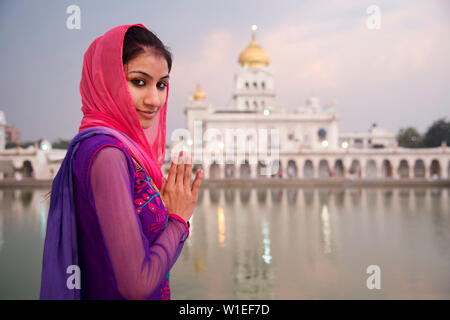 A young woman worshipping at a Sikh temple in Delhi, India, Asia - Stock Photo