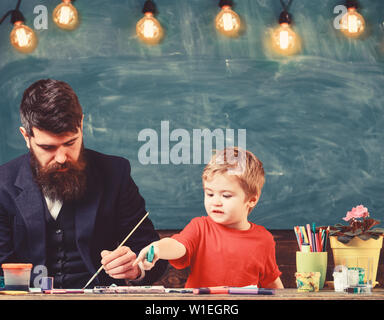 Teacher with beard, father teaches little son to draw in classroom, chalkboard on background. Child and teacher on busy face painting, drawing. Art lesson concept. Talented artist spend time with son.