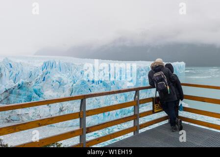 People at the Perito Moreno glacier viewing point, El Calafate, Santa Cruz, Argentina, South America - Stock Photo