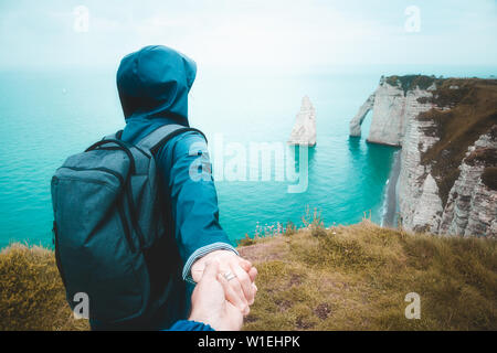 Follow me. Young woman in blue raincoat taking hand of her boyfriend walking to the edge of the cliff to watch a scenic seascape, Etretat, France. - Stock Photo