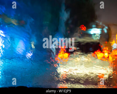 Blurred raindrops on car window with road light bokeh on rainy season abstract background. Water drop texture on the glass from the rain in car drivin - Stock Photo