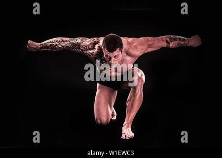 muscular man bodybuilder shows his muscles while standing on his knee. isolated on black background - Stock Photo
