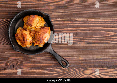 Fried chicken thighs in cast iron skillet - Stock Photo