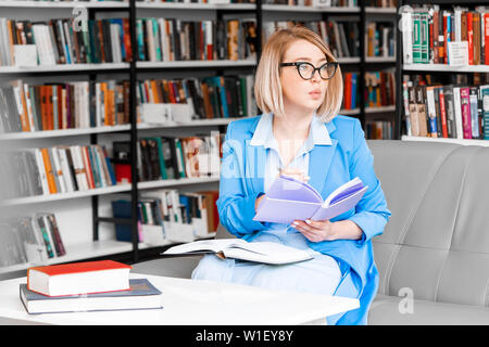 Young pensive attractive woman in formal attire makes some notes in notepad at library. - Stock Photo