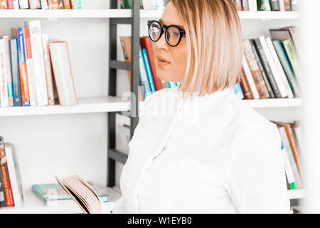 Young pensive attractive woman with glasses in formal clothes reading a book at library. - Stock Photo