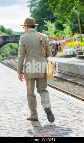 Kidderminster, UK. 29th June, 2019. Severn Valley Railways 'Step back to the 1940's' gets off to a fabulous start this weekend with costumed re-enactors playing their part in providing an authentic recreation of wartime Britain. Rear view of a man dressed in 1940s fashion walks along the platform of a rural, vintage railway station in the sunshine, waiting for the next steam train arrival. Credit: Lee Hudson - Stock Photo