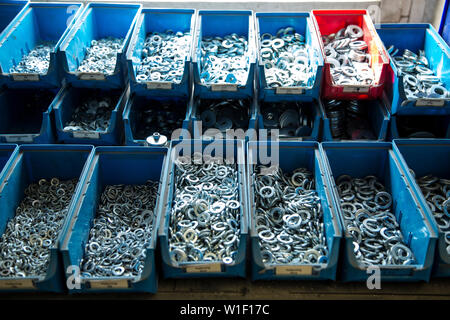 Containers with metal nuts - Stock Photo