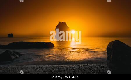 Sunset over rock formations, Reynisfjara beach, South Coast, Iceland - Stock Photo