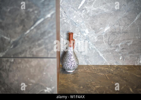 A beautiful antique jug , a vase stands in the corner of the room on a marble table. - Stock Photo