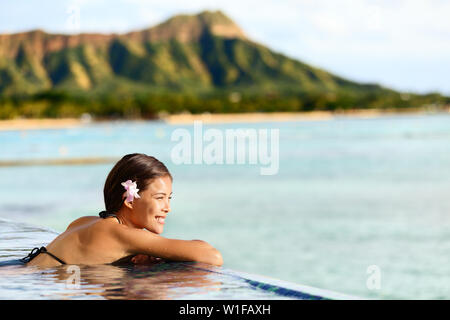 Hawaii beach travel vacation woman swimming relaxing at luxury pool hotel resort. Asian young adult on Waikiki beach, Honolulu, Oahu on exotic holidays - Stock Photo
