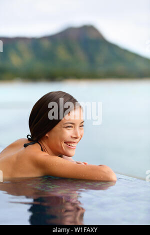 Holiday woman swimming at beach on Hawaii travel. Asian chinese young lady relaxing in infinity pool in luxury hotel resort on Waikiki beach in Honolulu, Oahu, Hawaii, USA. - Stock Photo