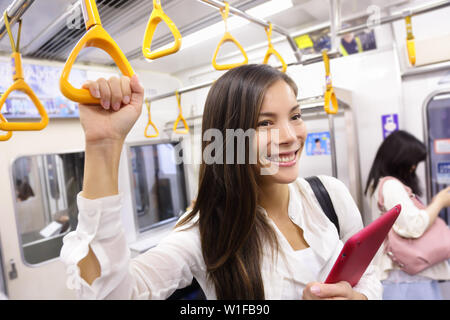 Subway commuter woman on Japanese public transport in Tokyo, Japan. Tourist using Japan's capital city metro system to commute. Portrait of happy asian lady holding handhold inside the wagon.