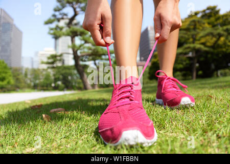 Runner getting ready for jogging tying running shoes laces - Woman preparing before run putting on trainers in japanese park near Ginza in Tokyo, Japan - Stock Photo