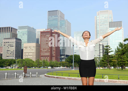 Happy free businesswoman cheering open arms in achievement and success, Japanese city woman carefree in front of Tokyo downtown skyline from the outer imperial palace gardens. - Stock Photo
