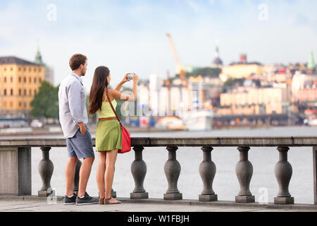 Europe travel tourist people taking pictures. Tourists couple in Stockholm taking smartphone photos having fun enjoying skyline view and river by Stockholm's City Hall, Sweden. - Stock Photo