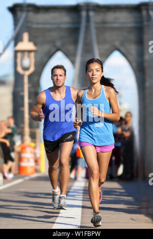 New York runners running training on Brooklyn bridge NYC during busy rush hours with tourists. Fit young couple doing their workout routine on a summer day. - Stock Photo