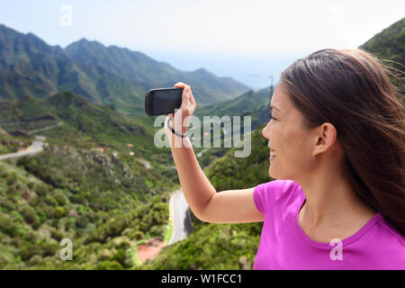 Girl taking smartphone picture of mountain nature. Female tourist traveling on road trip or hike in mountainous Anaga of Tenerife, Canary islands. Summer vacations. - Stock Photo
