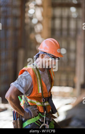 Dirty mid-adult construction worker wearing a helmet and hi-visibility vest while on a construction site. - Stock Photo