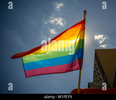 A rainbow flag flies from a business in New York on Thursday, June 27, 2019 in advance of the Stonewall 50/ World Pride parade. (© Richard B. Levine) - Stock Photo