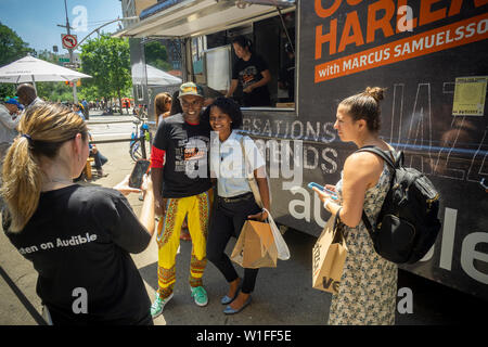 "Celebrity Chef Marcus Samuelsson greets visitors to the Audible food truck serving samples of his dishes in Union Square in New York on Thursday, June 27, 2019. Samuelsson voices Audible's audiobook adaptation, ""Our Harlem"", of his Red Rooster Cookbook adding interviews. (© Richard B. Levine) - Stock Photo"