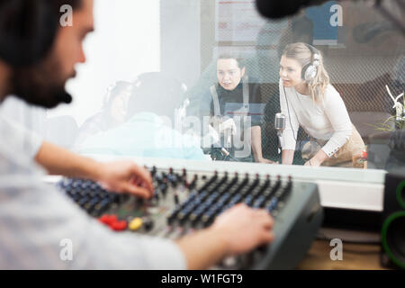 Presenters and guests in sound broadcasting station hosting live radio show. View from room where audio engineer controlling sound on air - Stock Photo