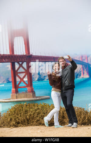 Tourists couple taking selfie photo in San Francisco by Golden Gate Bridge. Interracial young modern couple using smart phone by famous american landmark. Asian woman, Caucasian man. - Stock Photo