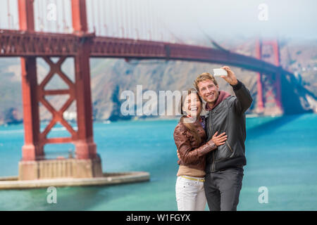 Happy young couple tourists taking selfie in San Francisco by Golden Gate Bridge. Interracial young modern couple using smart phone. Asian woman, Caucasian man. - Stock Photo