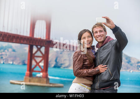 Couple tourists taking selfie photo in San Francisco by Golden Gate Bridge. Interracial young modern couple using smart phone by famous american landmark. Asian woman, Caucasian man. - Stock Photo