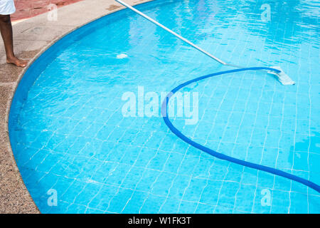 Man cleaning a swimming pool in summer. Cleaner of the swimming pool. - Stock Photo