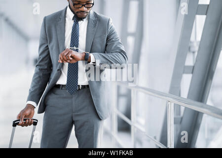 Businessman Checking Time On Watch, Walking In Airport - Stock Photo