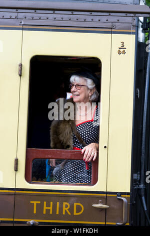 Kidderminster, UK. 29th June, 2019. Severn Valley Railways 'Step back to the 1940's' gets off to a fabulous start this weekend with costumed re-enactors playing their part in providing an authentic recreation of wartime Britain. Woman in 1940s fashion leans out of vintage railway carriage to look out of train window. Credit: Lee Hudson - Stock Photo