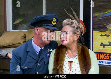 Kidderminster, UK. 29th June, 2019. Severn Valley Railways 'Step back to the 1940's' gets off to a fabulous start this weekend with costumed re-enactors playing their part in providing an authentic recreation of wartime Britain. Man in military RAF uniform & woman in 1940s fashion stare lovingly at each other as they wait together at vintage train station. Credit: Lee Hudson - Stock Photo